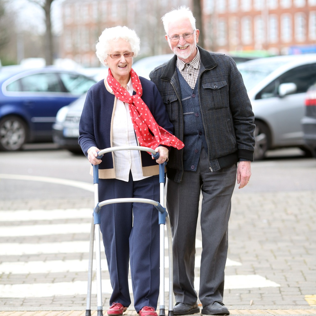 An elderly couple walk together, the lady is using a stylish silver and navy blue walking frame. The lady wears a matching navy outfit and a dark pink scarf which blows in the wind,. The man wears a button up shirt and has bright white hair. They are both smiling .