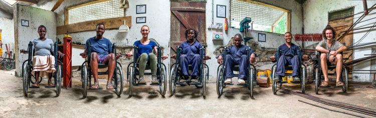 Seven people from the safariseat wheelchair team sat in the kenyan workshop smiling