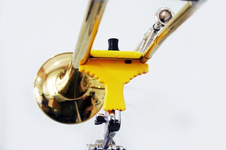 A bird shaped clip holding up a trombone