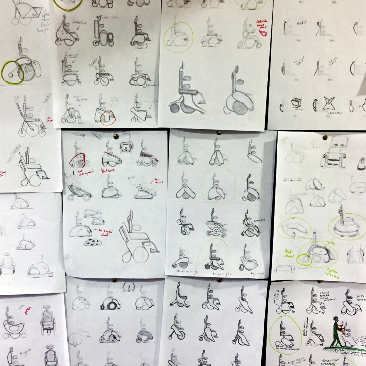 A wall covered in sketches from the ideation phase of the children's wheelchair design