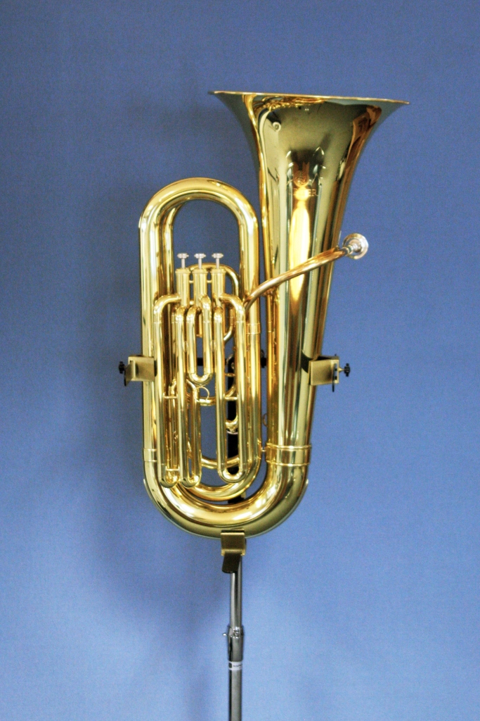 A tuba being held up on the stand.