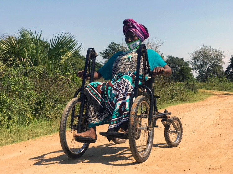 A local Kenyan lady with a bright purple turban and teal patterned dress drives her Safariseat at speed down a dusty track, leaving a cloud of golden dust in the air behind her.