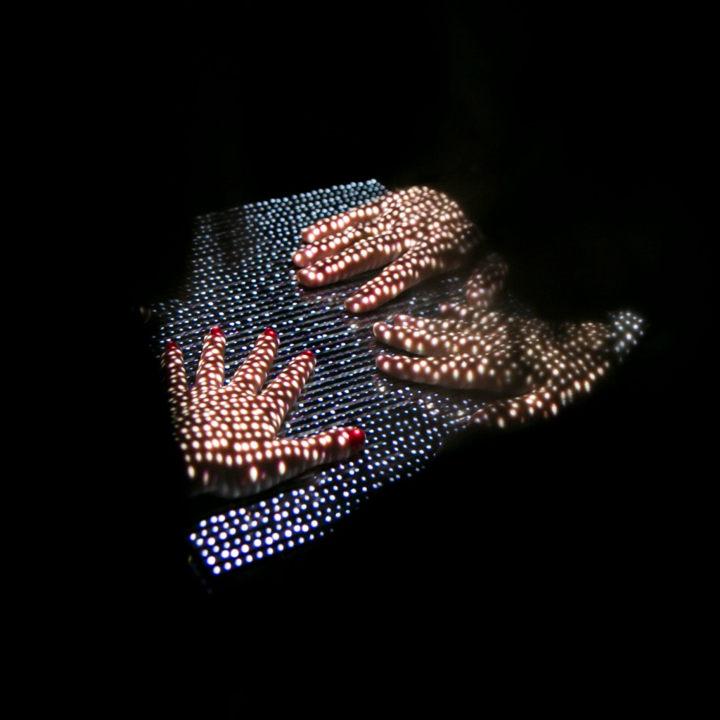 three hands placed on a block are lit up by a sheet of lights projecting dots onto them. the result looks very abstract