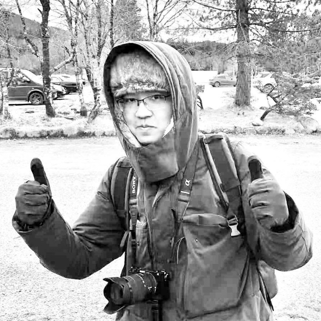 A young man standing in the snow with his gloved thumbs up, wearing a large fur-lined coat with the hood over his head. He wears thin framed glasses and has a professional camera hung around his neck, and a rucksack on his back.